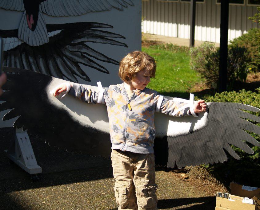 child measuring wingspan