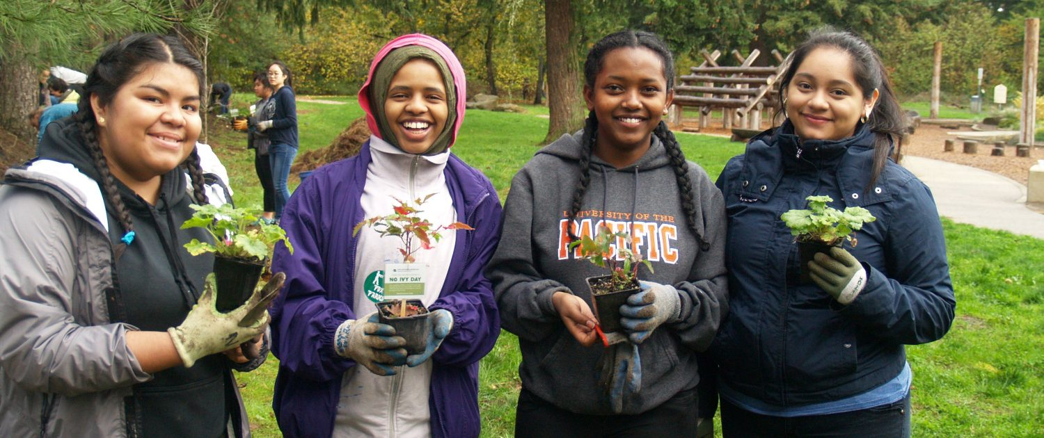 Four girls holding seedlings to be planted